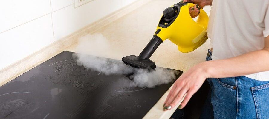 Canva-Woman-cleaning-kitchen-with-steam-cleaner-900x520